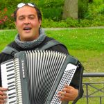 man playing accordion in a park