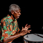 black man with colourful shirt playing djembe