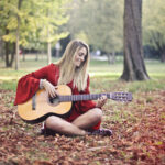 young woman playing guitar sitting in autumn leaves