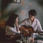 An Asian man playing a guitar and singing with a woman