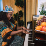 woman in colourful dress playing piano